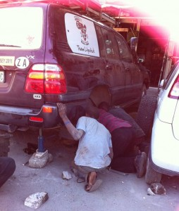 Three of Dar es Salaam's highly motivated car repair technicians changing shocks and springs for team Lipstick. Note their adjustable support structures..