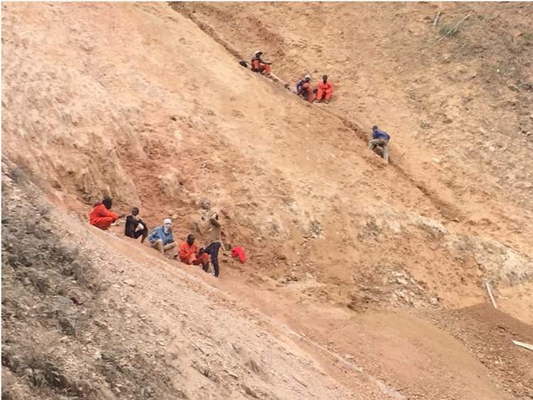 Congo workers securing the mountain from falling onto the roads